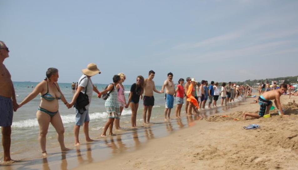 Un centenar de veïns s'uneixen en una cadena humana per reclamar més protecció per la Platja Llarga