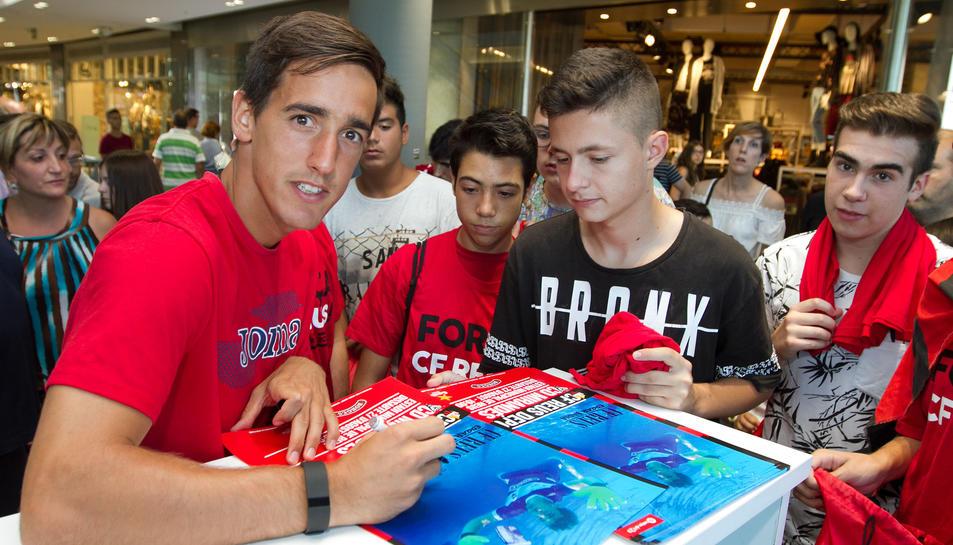 Edgar Badia signa per als aficionats alguns pòsters on apareix vestit de curt i submergit a l'aigua.