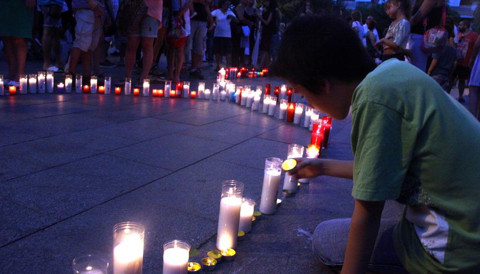 Imatge d'arxiu d'un nen posant espelmes pels assassinats masclistes de dues dones i dos menors a Castelldefels el 2015.