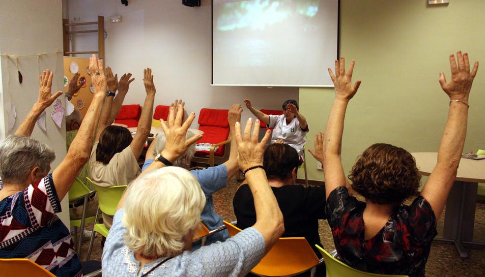 Un grup d'avis aixequen les mans seguint les instruccions d'una terapeuta en un taller de psicomotricitat a l'associació AFAB per a malalts d'Alzheimer.