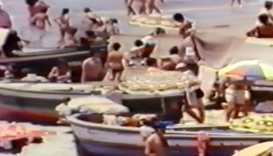 Una imatge del vídeo, on es poden veure persones a la platja amb les barques sobre l'arena.