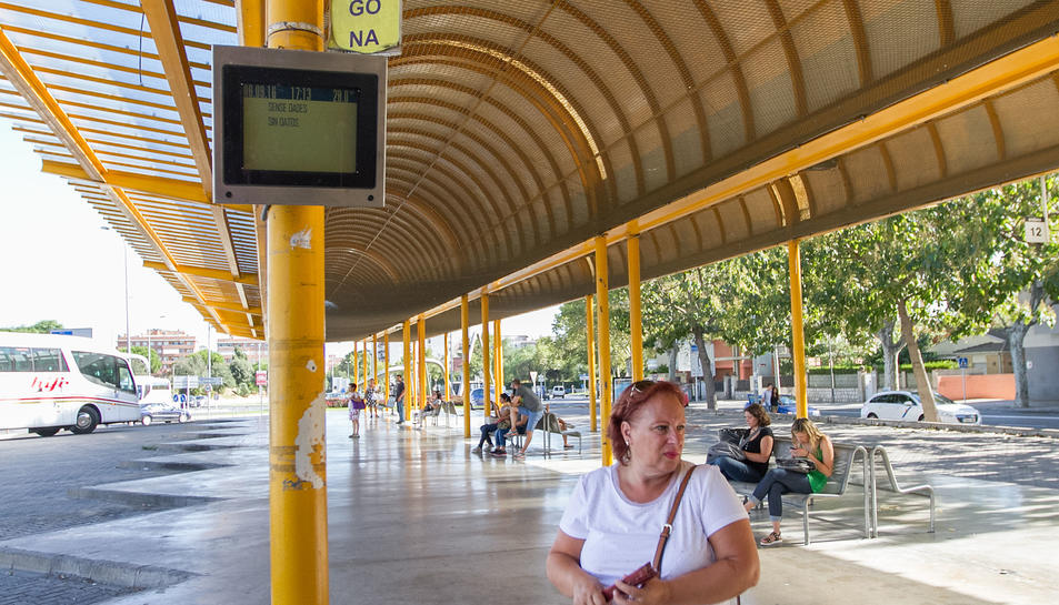 Una passatgera al costat de la pantalla d'informació de la línia Reus-TGN, a l'Estació d'Autobusos.