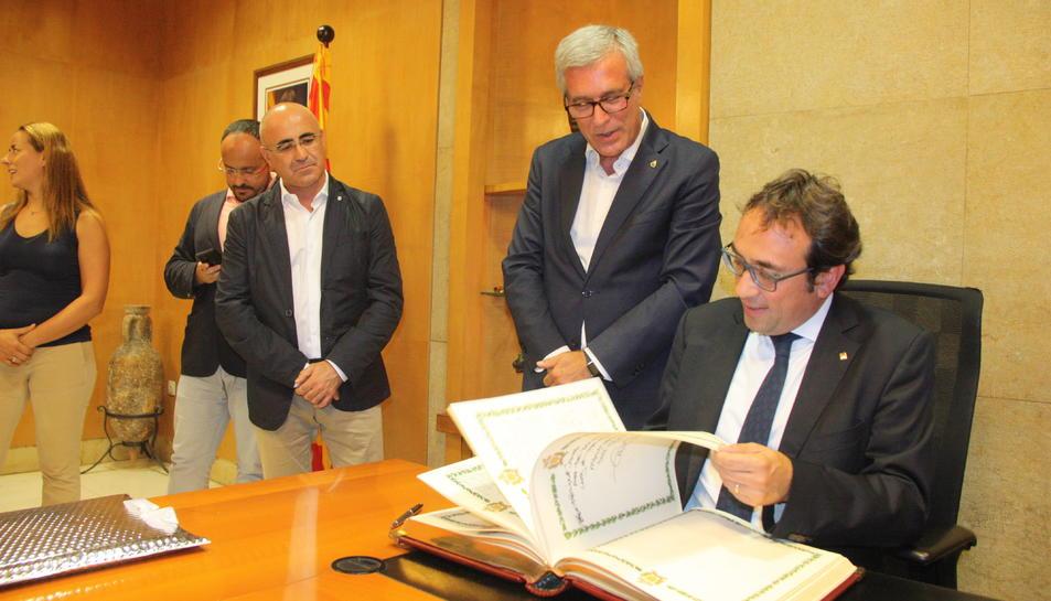 El conseller de Territori i Sostenibilitat, Josep Rull, fullejant el Llibre d'Honor de l'Ajuntament de Tarragona, sota la mirada de l'alcalde, Josep Fèlix Ballesteros.