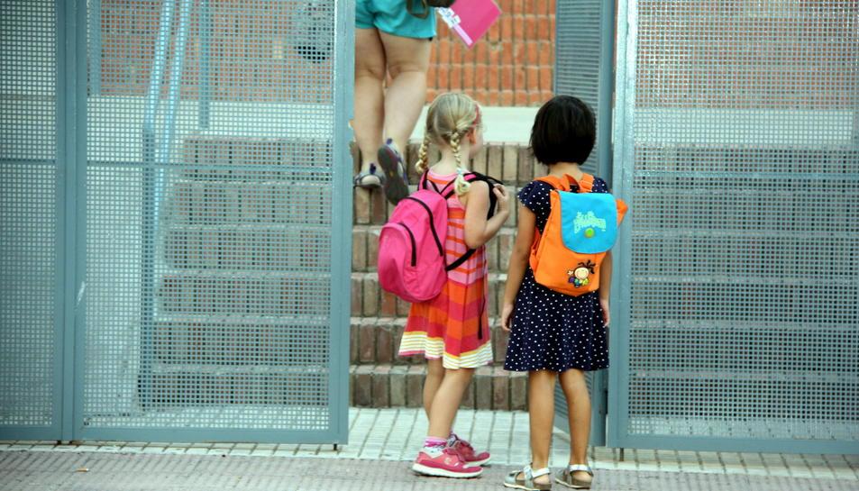 Dues nenes d'esquema amb les motxilles a punt d'entrar a l'escola del Pinell de Brai en el segon dia de curs. Imatge del 13 de setembre de 2106 (horitzontal)