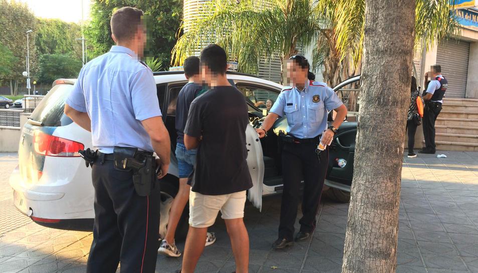 Alguns dels joves entrant al cotxe dels Mossos d'Esquadra.