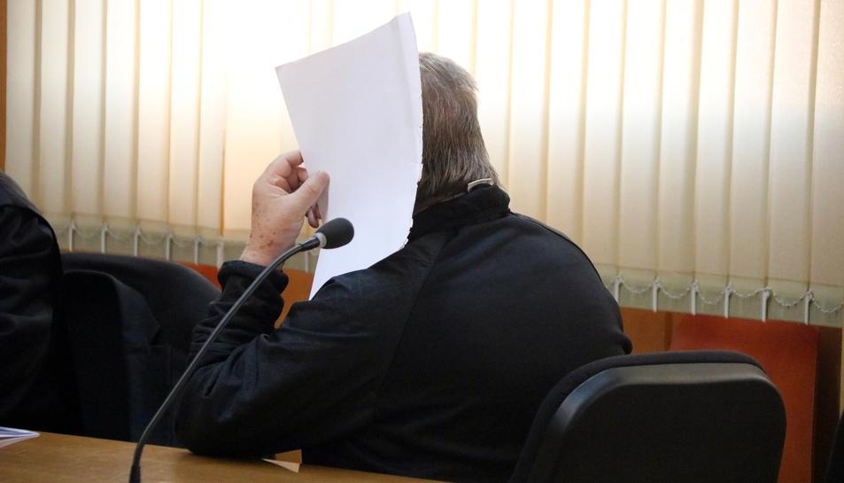Primer pla de l'acusat tapant-se la cara amb un full de paper a la sala de vistes de l'Audiència de Tarragona.