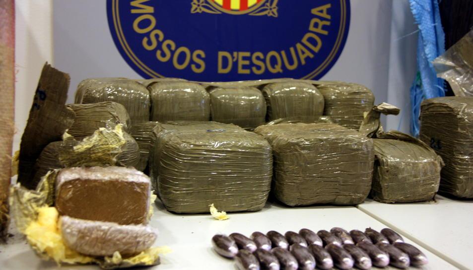 Pla detall dels paquets d'haixix interceptats a Deltebre en les diversos embalatges en què es van decomissar i amb l'escut dels Mossos al fons. Imatge del 7 d'octubre de 2016 (horitzontal)