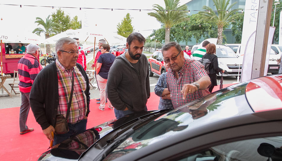 Visitants a la fira en un estand d'automòbils.