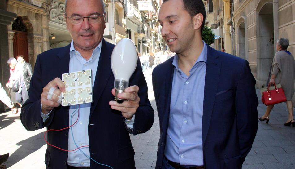 Pla mig de l'alcalde de Reus, Carles Pellicer, i del regidor de Medi Ambient, Daniel Rubio, mostrant la bombeta que se substituirà per llum led, al carrer de Llovera de Reus, un dels carrers que renovarà enllumenat, l'11 d'octubre del 2016
