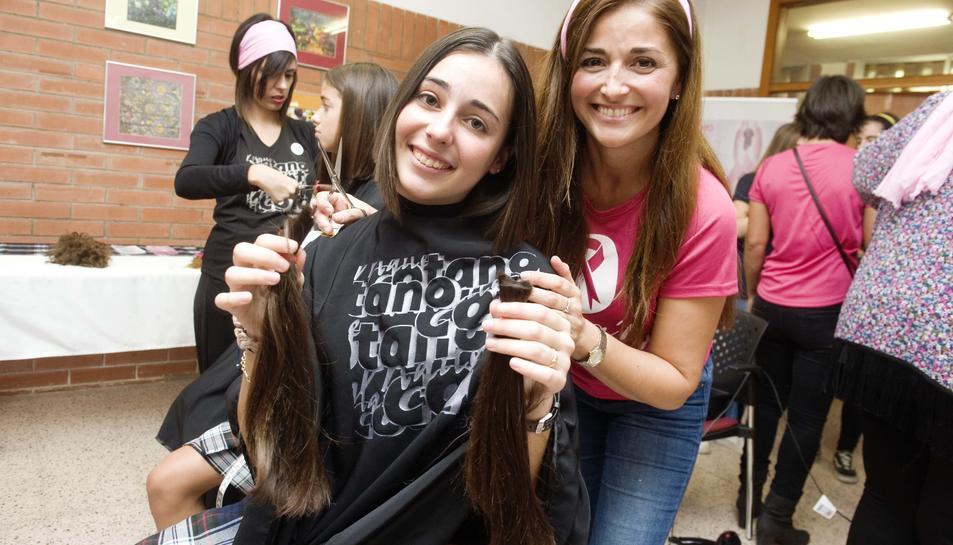 Una alumna sostenint la cua de cabell que s'ha tallat per donar-la a la fundació Mechones solidarios.