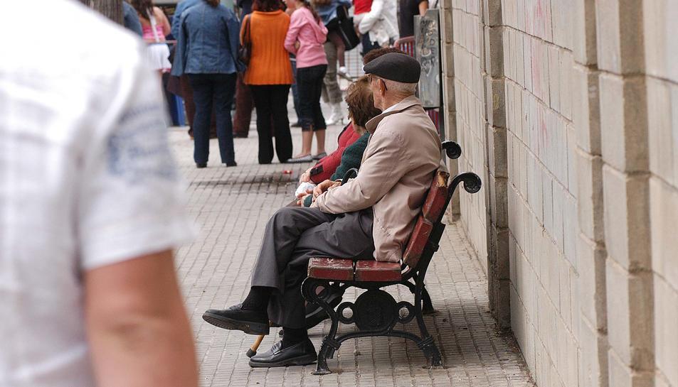 Imatge d'arxiu de gent gran asseguda en un banc.