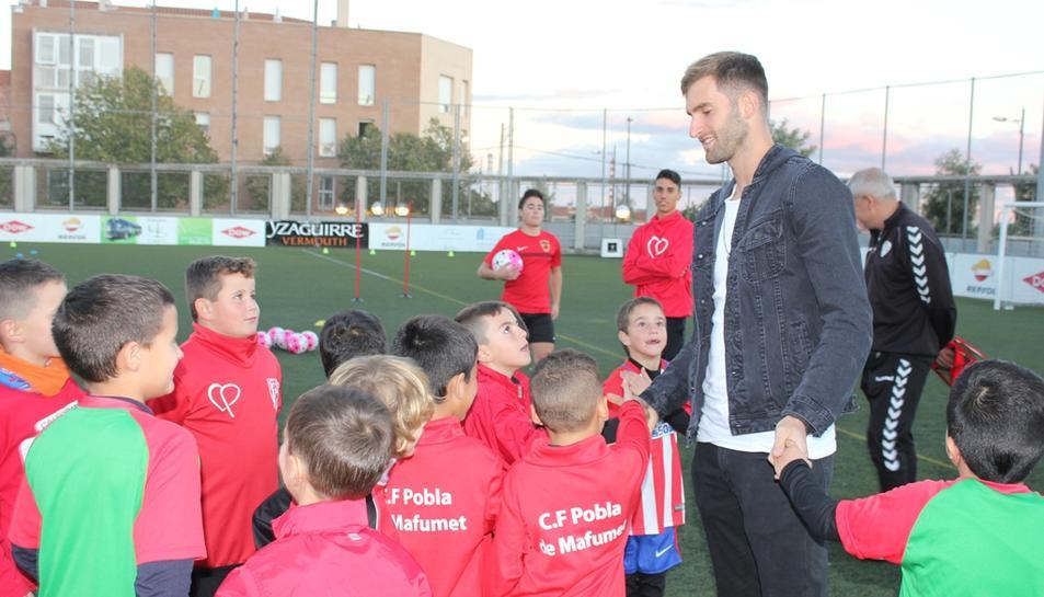 El jugador blanc-i-blau amb nens del club.