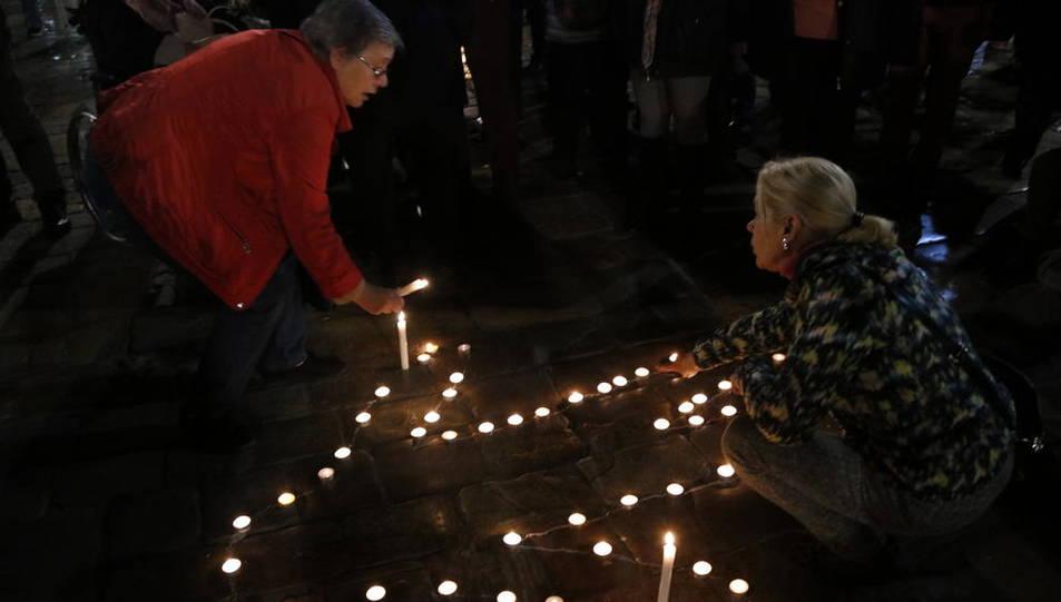 Pla tancat de dues persones encenent espelmes per formar una silueta humana a la plaça del Mercadal de Reus el 16 de novembre de 2016