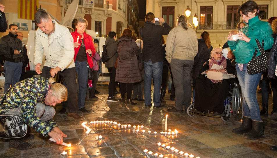 Una de les assistents col·locant una espelma a la figura.