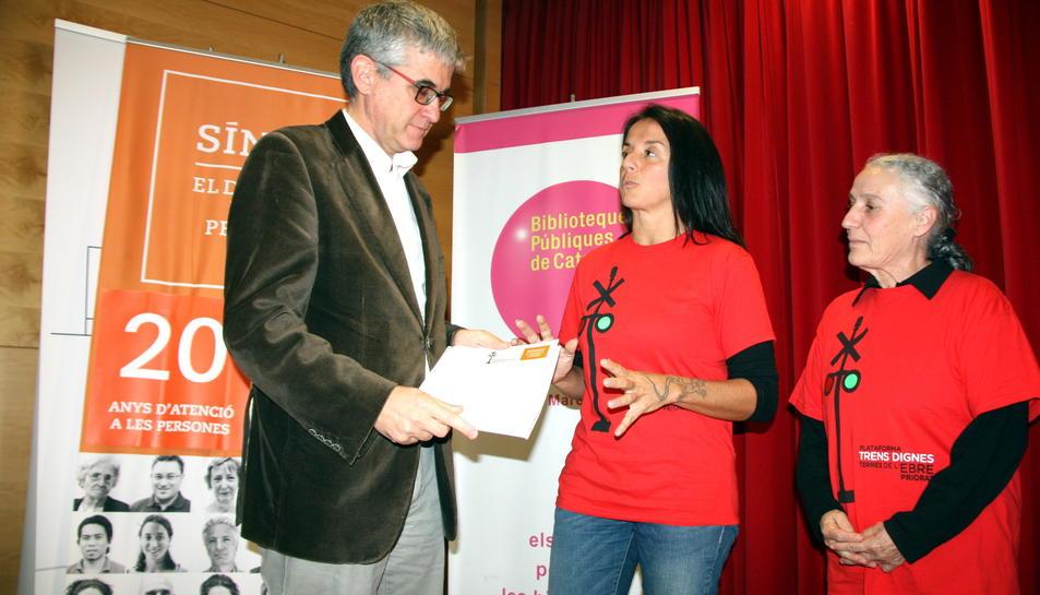 Dues representants de Trens Dignes, entre elles la portaveu Montse Castellà, entregant el plec de queixes al'adjunt general del Síndic de Greuges.