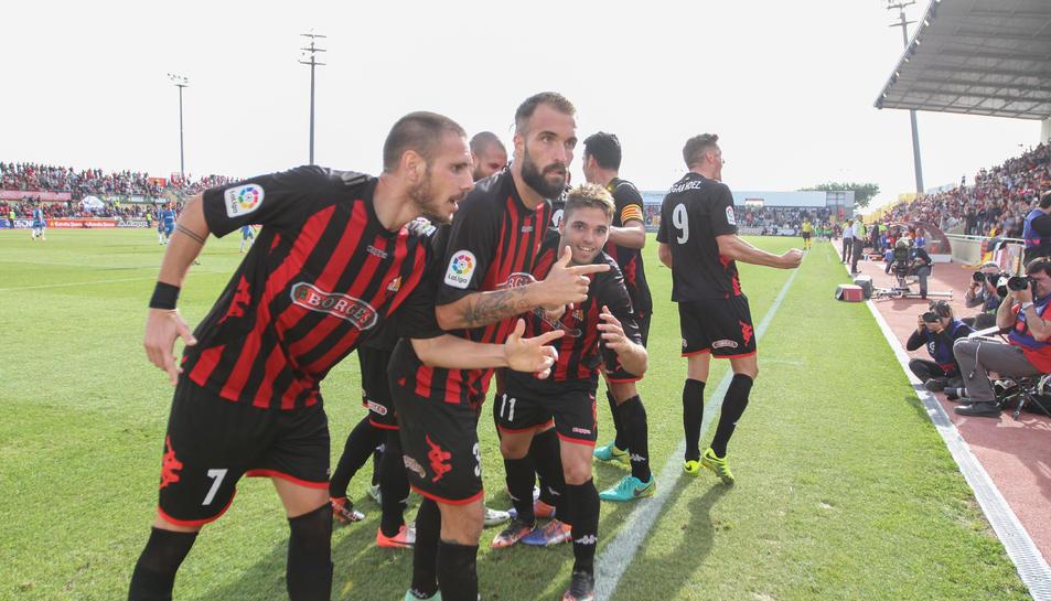 Jugadors roig-i-negres van acostar-se a la banda després del gol que significava la victòria i van quedar-se quiets per uns instants.