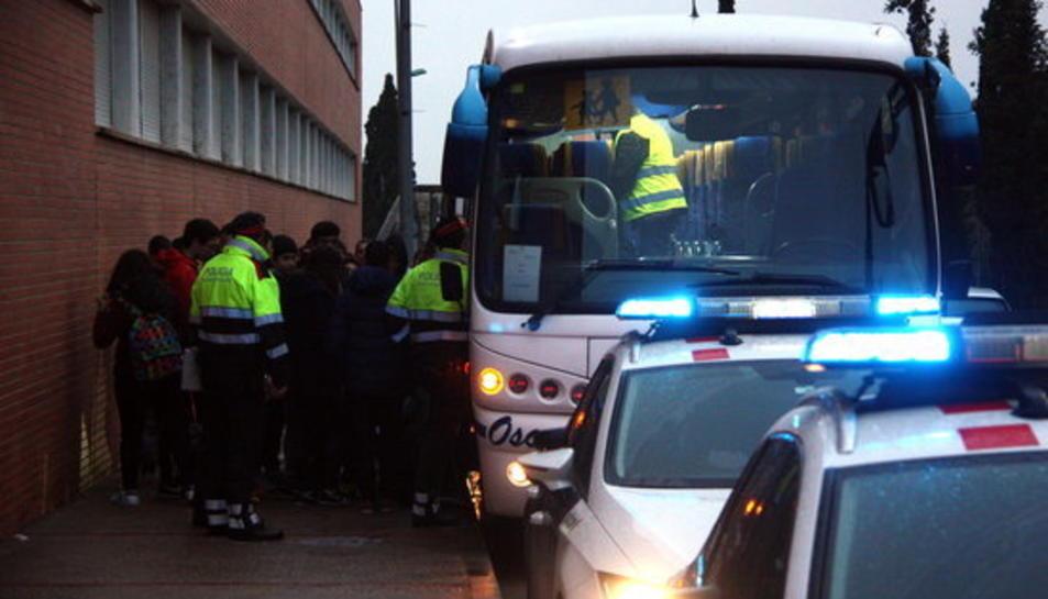 Un grup d'escolar baixant de l'autocar a les portes de l'IES Roquetes mentre els Mossos d'Esquadra inicien el control dels vehicles.