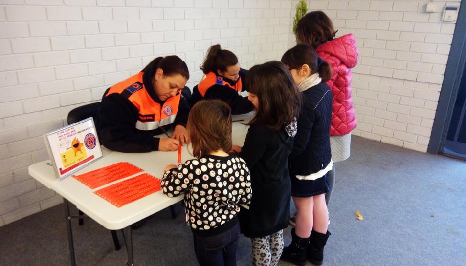 Voluntaris de Protecció Civil reparteixen les polseres entre els infants