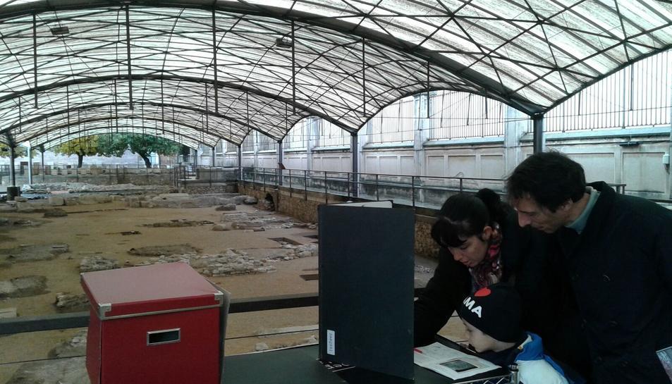 Luis i Ainhoa, amb un dels seus fills, consulten informació per fer el taller.