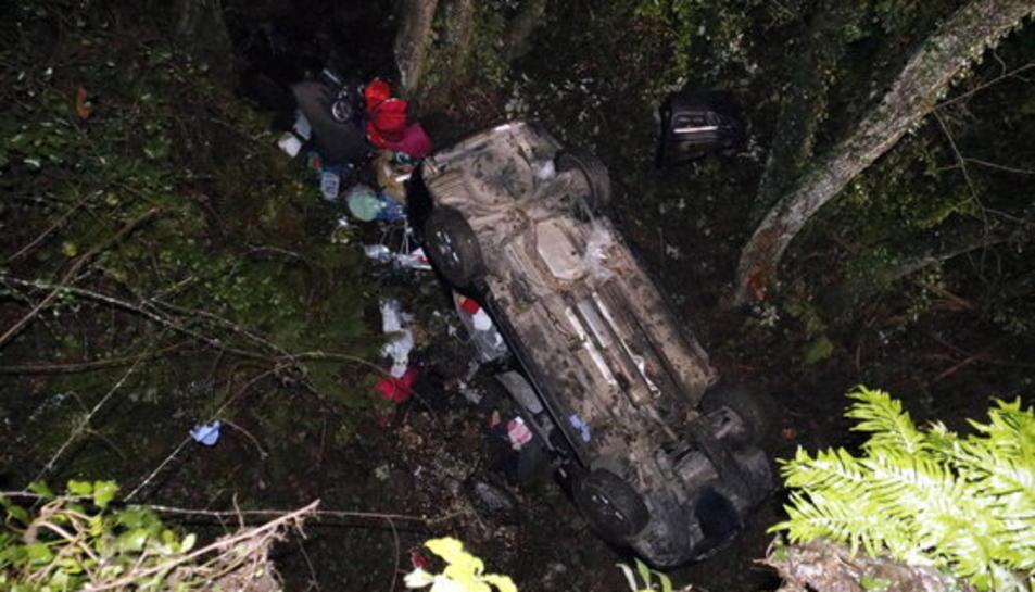 Pla general del cotxe accidentat a Susqueda, cap per avall, amb equips d'emergències treballant.