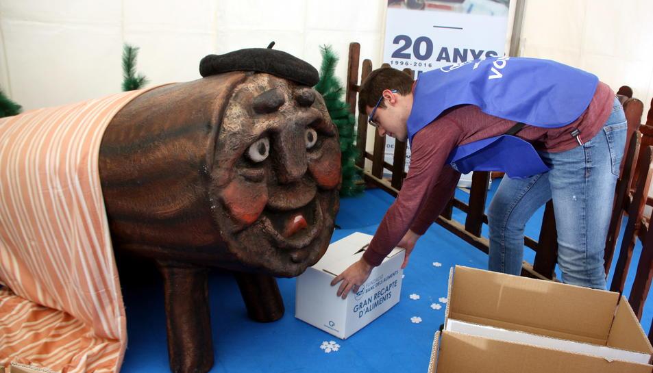 Oscar Ologaray, coordinador de la delegació ebrenca del Banc dels Aliments, diposita una caixa al costat del Tió Solidari.