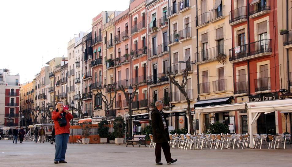 Un parell de turistes passejant i fent fotos amb el mòbil a la plaça de la Font de Tarragona, en una imatge del 14 de desembre del 2016