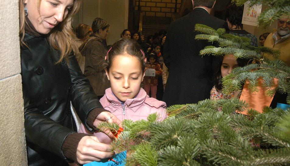 Imatge d'una nena penjant el seu missatges a l'Arbre dels Desitjos en una edició anterior.