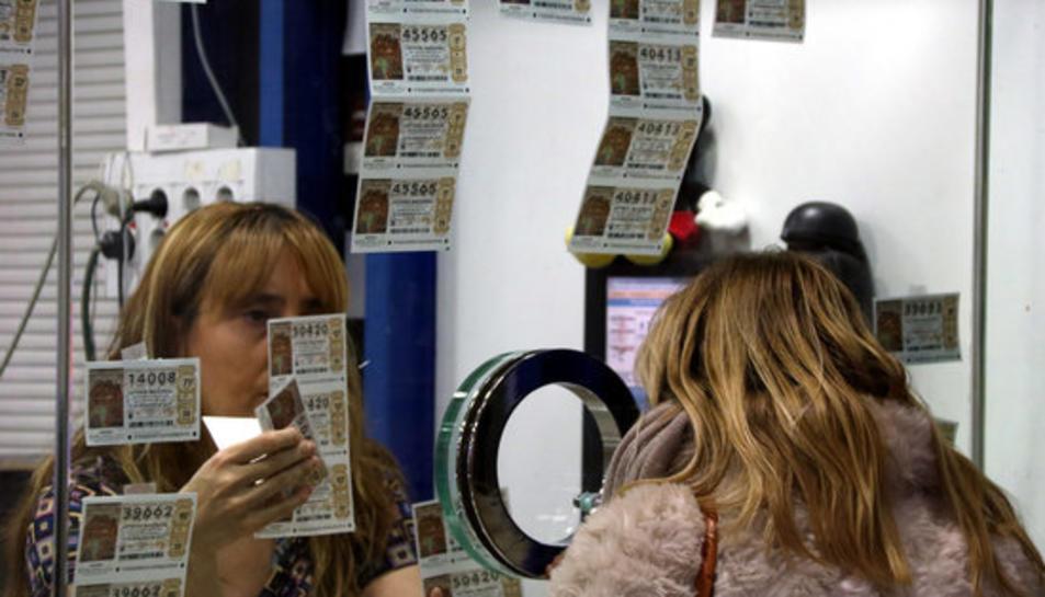 Primer pla de la treballadora d'una administració de loteria amb una clienta comprant un dècim el 19 de desembre de 2016