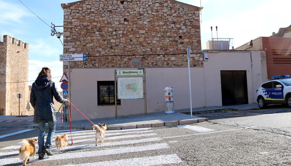 Pla general de l'exterior de la comissaria de la Policia Local de Montblanc i del magatzem on es guarden temporalment gossos abandonats, i d'una noia passejant tres gossos per la zona, en una imatge publicada el 26 de desembre del 2016