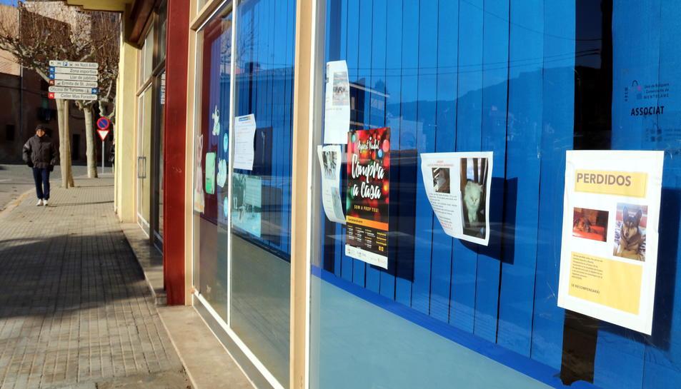 Imatge exterior d'un cartell de dos gossos desapareguts a Montblanc, penjat als vidres d'una clínica veterinària de la localitat, i un anunci d'un gat, també perdut, i altres informacions, en una imatge publicada el 26 de desembre del 2016