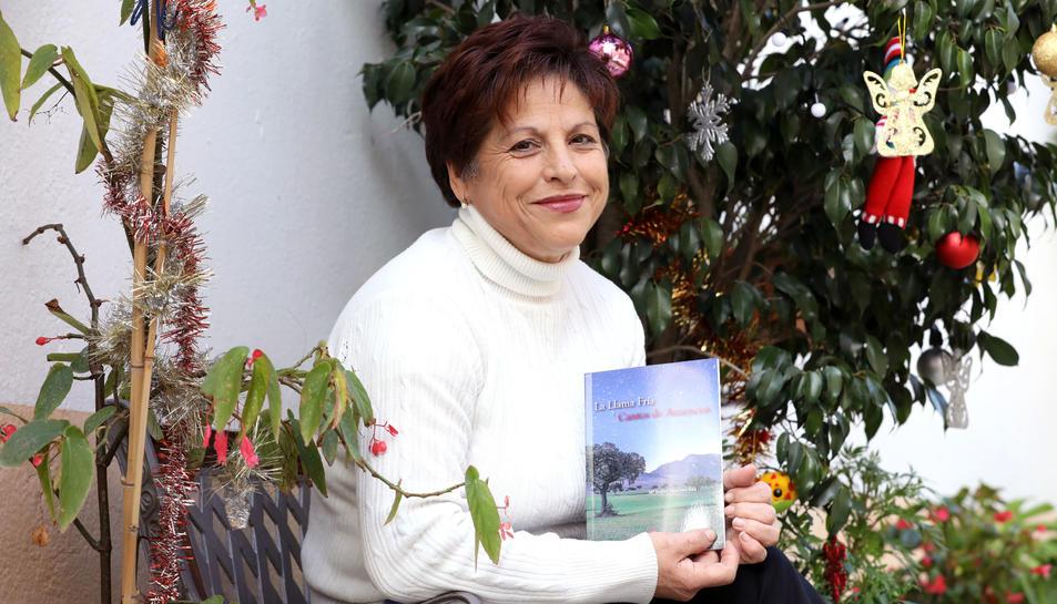 Maria Isabel a l'entrada de casa seva, amb el seu primer llibre, 'La Llama Fría y Cantos de Ausencias'.