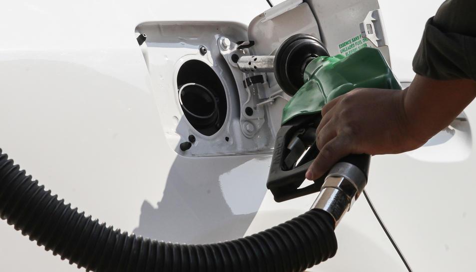 Una persona posa gasolina al seu vehicle.