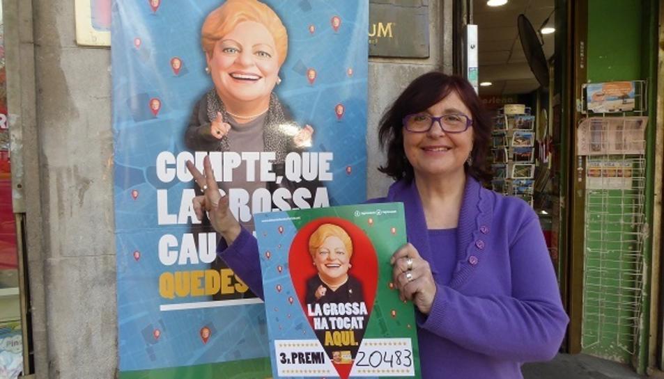 La Cèlia Rovira a fora de l'establiment amb el cartell de la Grossa de Cap d'Any.