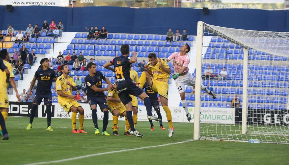 El porter del CF Reus, Edgar Badia, salta en una acció a pilota aturada per mirar de refusat el tret d'un oponent de l'UCAM Murcia.