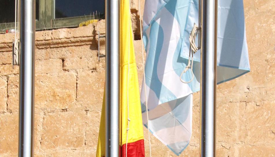 Pla obert de l'alcalde de Torredembarra, Eduard Rovira, lligant la bandera espanyola al pal.