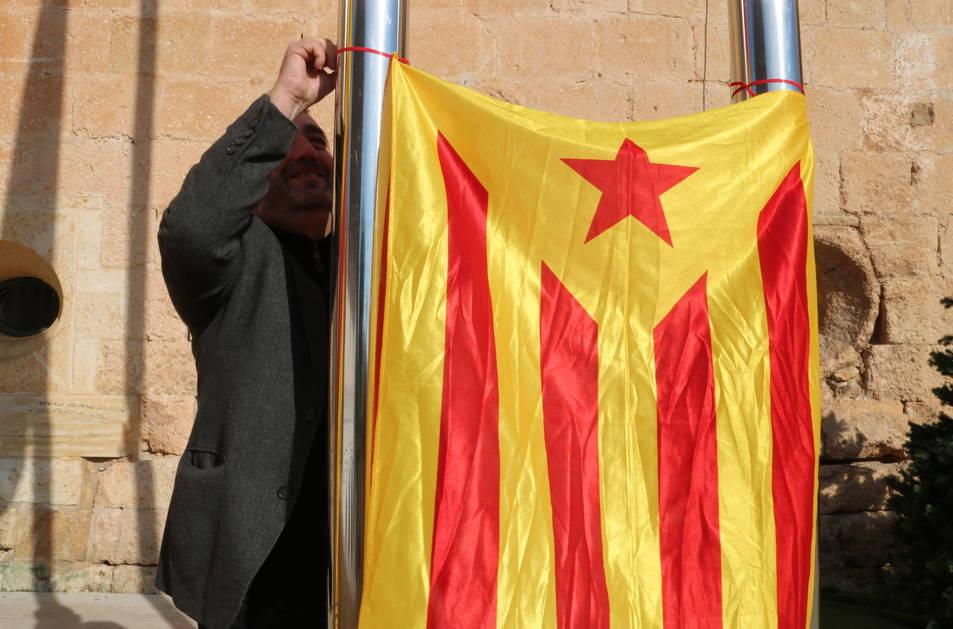El portaveu d'Alternativa Baix Gaià, Lluís Suñé, penja una estelada entre dos pals de l'Ajuntament de Torredembarra.
