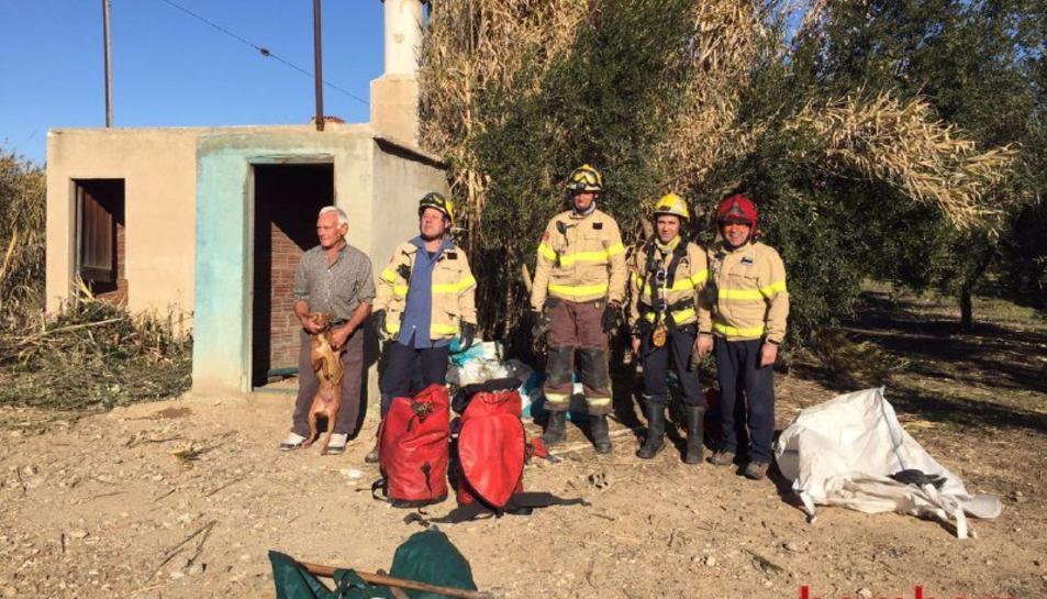 Els Bombers amb el gos rescatat.