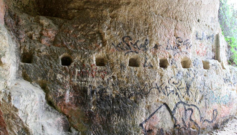 Aspecte que ofereix una de les coves que constitueixen la pedrera romana. A la dreta, la natura gairebé oculta l'accés a una cavitat, alguns carreus dispersos pel terra i pintades i elements realitzats pels picapedrers en una de les Coves del Llorito.