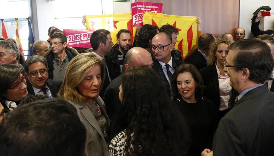 Santamaría, Báñez i Millo saludant diversos assistents a l'acte d'inauguració amb estelades al fons.
