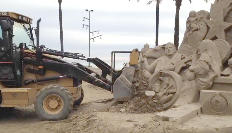 Imatge de la màquina excavadora enderrocant el pessebre de sorra.