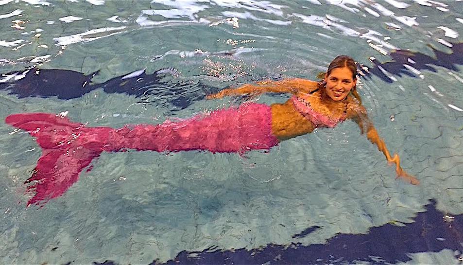 La jove sirena a la piscina amb la cua de color rosa.