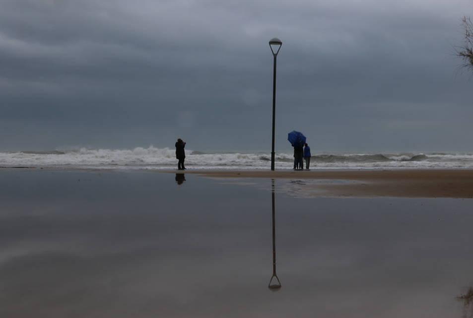 Pla obert d'un grup de persones a la platja de Baix a Mar després del temporal a Torredembarra. Imatge del 22 de gener de 2017
