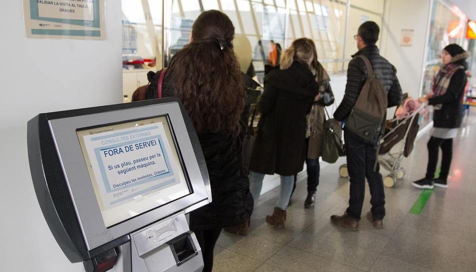 Diversos usuaris en el servei del punt d'informació al costat de la màquina fora de servei, ahir.
