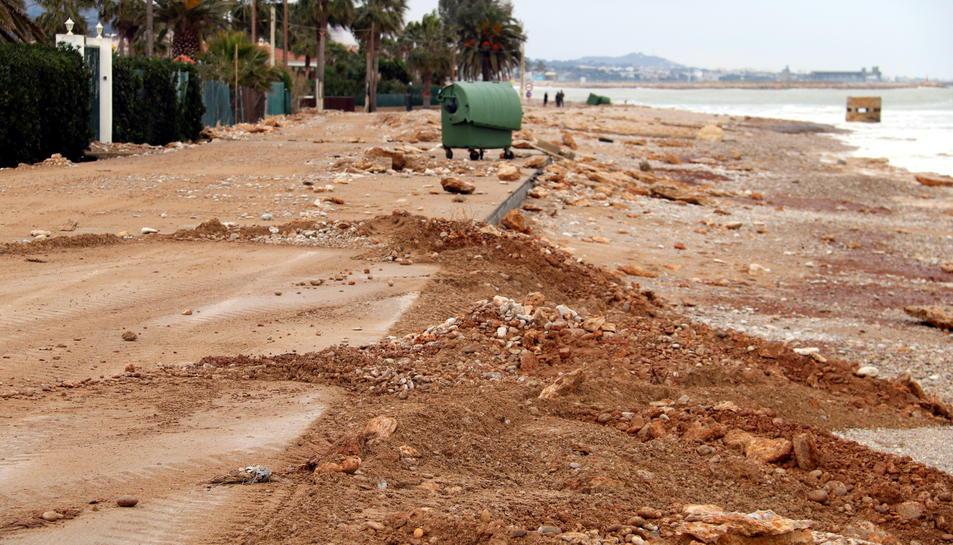 Carretera d'accés a la Platjola de les Cases d'Alcanar plena de sorra i roques mentre els operaris ho netegen.