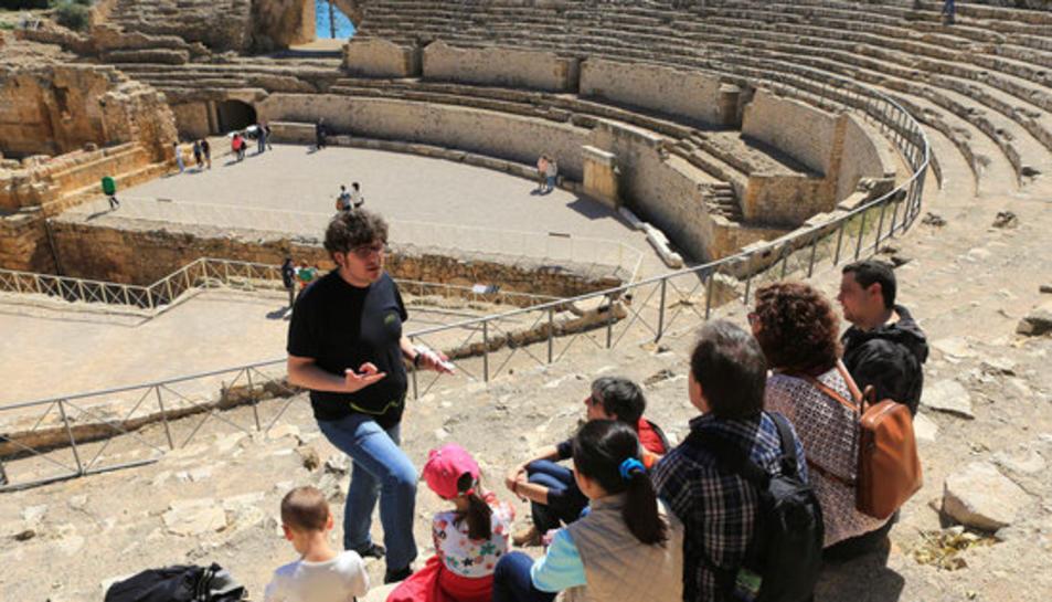 Pla obert de diversos turistes, d'esquena, gaudint d'una visita guiada a l'amfiteatre de Tarragona.