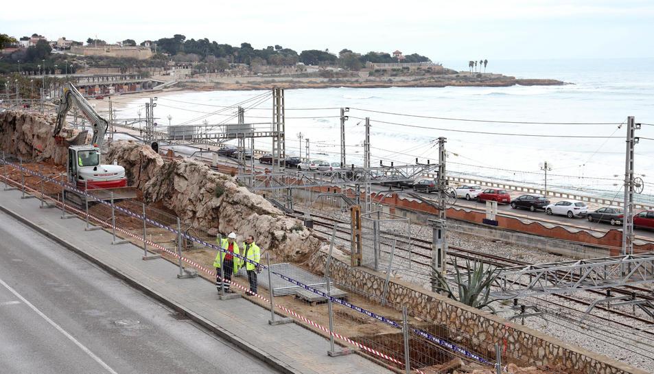 Uns operaris treballan en el terreny on es farà la cimentació de les columnes que soportaran la passarel·la.