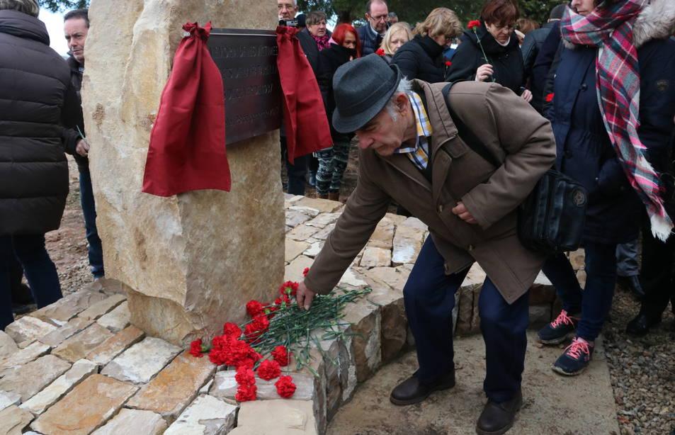Un home posa un clavell roig al monument que commemora els Fets de la Fatarella.