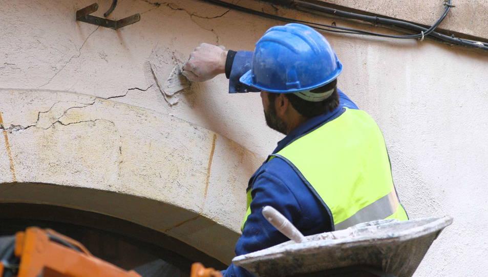Un operari posa testimonis de guix damunt les esquerdes aparegudes en la façada d'un edifici.