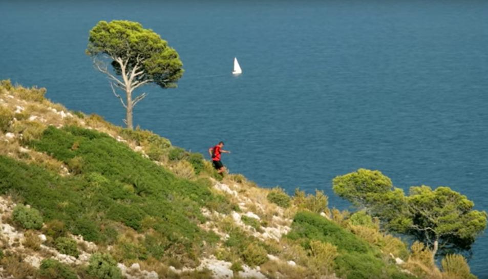 Una imatge extreta del vídeo, on el protagonista recorre una muntanya amb el mar de fons.
