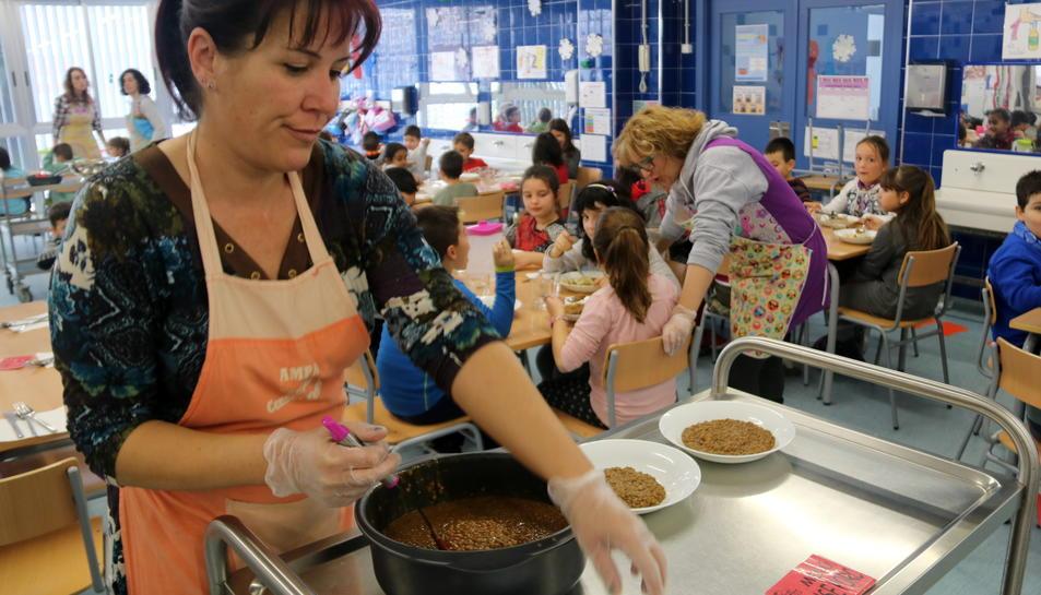 Una de les mares que donen suport diàriament a les monitores del menjador de l'Escola Consol Ferré, preparant els plats.